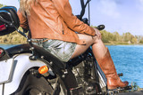 Biker girl in a leather jacket on motorcycle near river