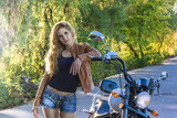 Sexy biker girl in a leather jacket posing motorcycle