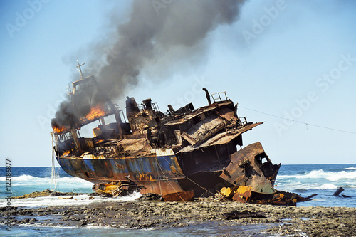 Foto op Canvas Schipbreuk Stranded fish cutter lying burning at a reef.