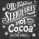 Old fashioned sleigh rides and hot cocoa on the farm. Chalkboard hand-lettering sign. Hand drawn typography with a mug of hot cocoa. Signpost on blackboard background with chalk
