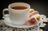 Mug of tea and Turkish delight with nuts on a plate, close-up, black background