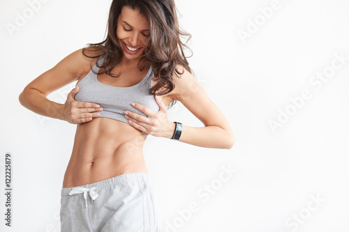fit woman showing her abs on white with copyspace