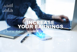 """Businessman is working in office, pressing button on virtual screen and selecting """"Increase your earnings"""". Business concept."""