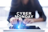 "Woman is using tablet pc, pressing on virtual screen and selecting ""Cyber Monday""."