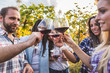 Friends standing in circle and toasting with wine in an Italian