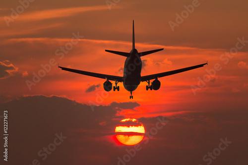 Plagát Airplane landing at sunset
