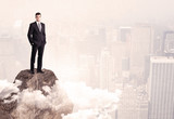 Happy businessman standing on stone top
