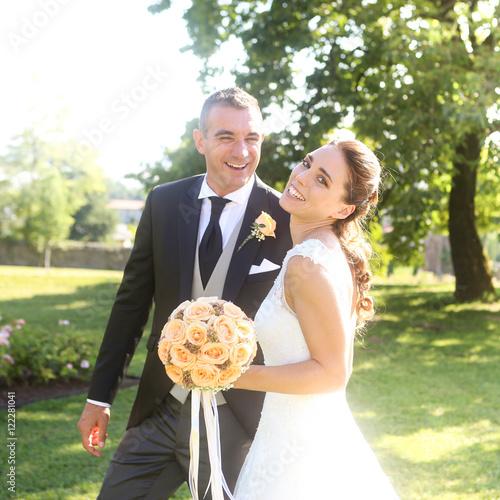 Zdjęcia Bellissimi sposi sorridono mentre passeggiano nel giardino