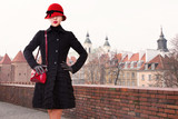 Fototapety Winter fashion in Europe, Poland Warsaw. Vintage look hat,red purse and black wool coat woman standing in the city.