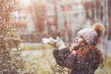 Little girl catches falling snowflakes.