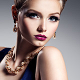 Pretty girl with beautiful gold jewelry and bright make-up