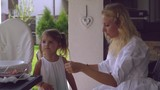 Mother with little daughter at the outdoor terrace in the garden. Little cute girl standing with young caucasian woman smiling. Beautiful adult blonde get a wave happy baby. Female wearing in white