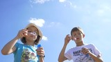 Boy And Girl Blowing Soap Bubbles Outdoors On A Sky Background, Slow Motion