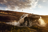 Car SUV overcomes water on the offroad background