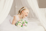 Little princess like a bride sitting on the bed with bouquet and