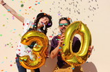Fototapety Cheerful couple celebrates a thirty years birthday with big golden balloons and colorful little pieces of paper in the air.