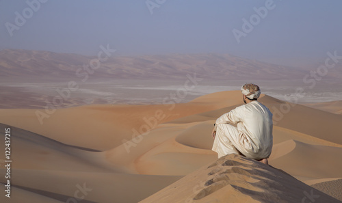 Fotobehang Abu Dhabi Man in kandura in a desert at sunrise