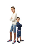 Tall teenager and little boy stand back to back with hands crossed on chest isolated on white background