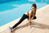 beautiful young woman streching by the swimming pool
