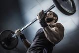 Hombre con grandes músculos levantando peso mientras entrena en el gimnasio. Ponerse en forma. - 122447406