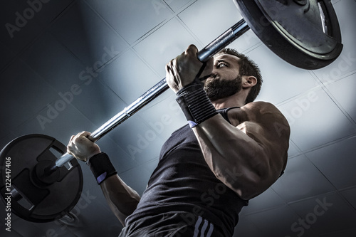 Hombre con grandes músculos levantando peso mientras entrena en el gimnasio Poster