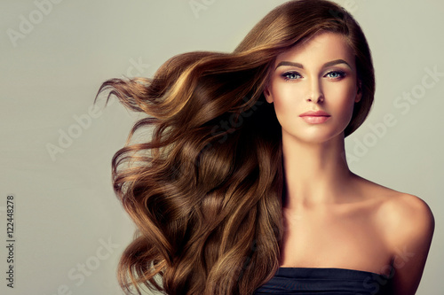 Beautiful model  girl with long wavy  and shiny  hair . Brunette woman  with curly hairstyle  © Sofia Zhuravetc