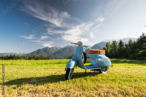 Foto op Canvas Scooter Blaue Vespa vor Bergkulisse auf Feld