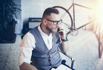 Bearded Businessman Making Great Business Idea Modern Workplace.Young Man Working Startup Desktop.Using Smartphone Call Meeting Partner.Guy Wearing White Shirt Waistcoat Work Office.Blurred Flares.