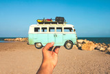 Toy minivan in hand on the background of sea, sand beach and blue sky