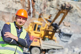 worker in front of heavy excavator and dumper truck