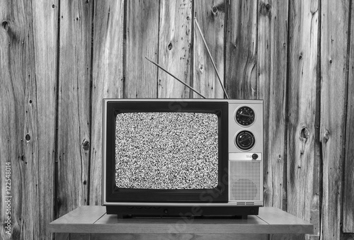 Vintage Television with Rustic Wood Wall and Static Screen in Black and White Poster