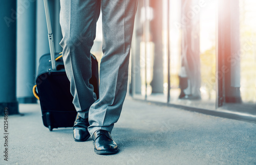 Business traveler pulling suitcase