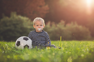 Toddler playing with a soccer ball in the sunset