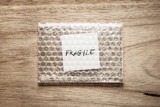 fragile, handwriting on white squre paper in bubble pack, rought wood background