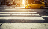 Focus on pedestrian lines in New york, with yellow cab in the ba