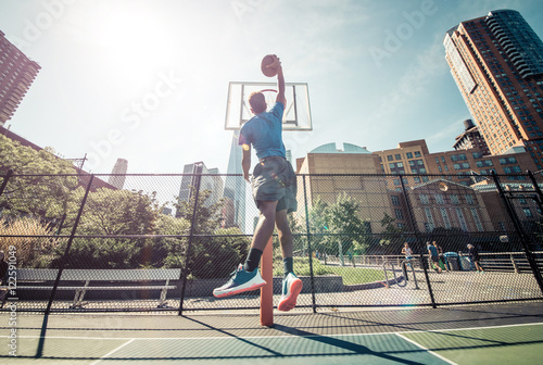 Poster Street basketball athlete performing huge slam dunk on the court