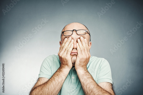 Tired middle-aged man rubbing his eyes