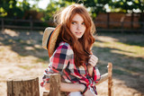Attractive redhead young woman cowgirl standing outdoors