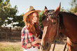 Woman cowgirl taking care of her horse on ranch