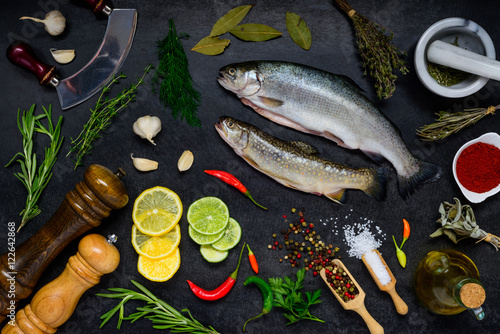 Plakat Trout Fish with Cooking ingredients on Dark Background