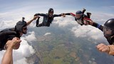 A group of friends holding hands teamwork skydiving