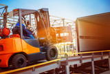 Forklift is putting cargo from warehouse to truck outdoors - 122678868