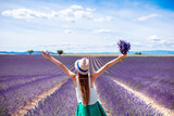 Young woman with raised hands holding lavender bouquet standing on the lavender field in Provence - 122682433