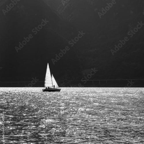 Sailing ship on the mountain lake. Sun reflected in water. Black and White - 122683856