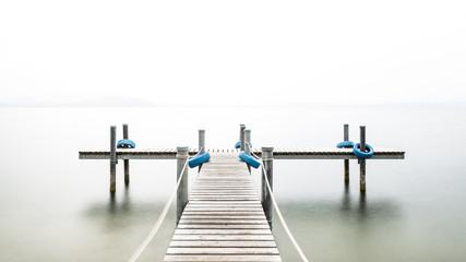 Autumn. Wooden pier on the lake. Fog. Long exposure.