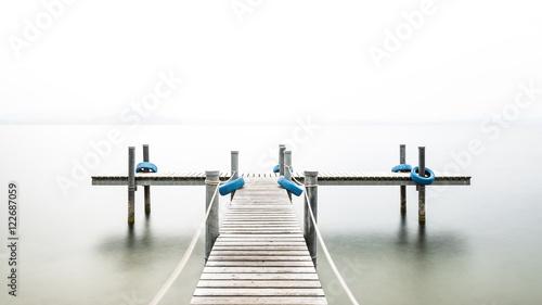 Autumn. Wooden pier on the lake. Fog. Long exposure.  - 122687059