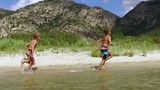 Children run along the coast on the water in slow motion