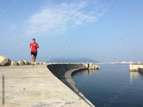 Zdjęcia na płótnie, fototapety, obrazy : Man running along harbor sea wall