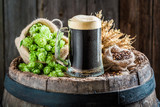 Dark beer with foam, wheat and hops on old barrel - 122698802