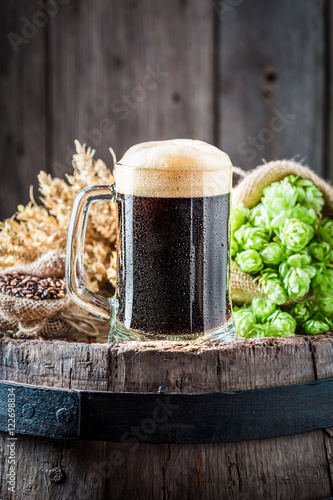 Fotografiet Pint of fresh dark beer with ingredients